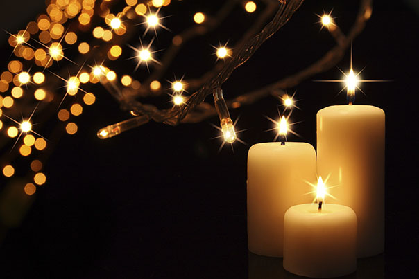 photo of three lit candles and starry lights