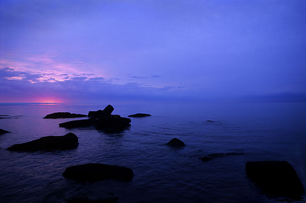 image of dark rocks near shore during sunset